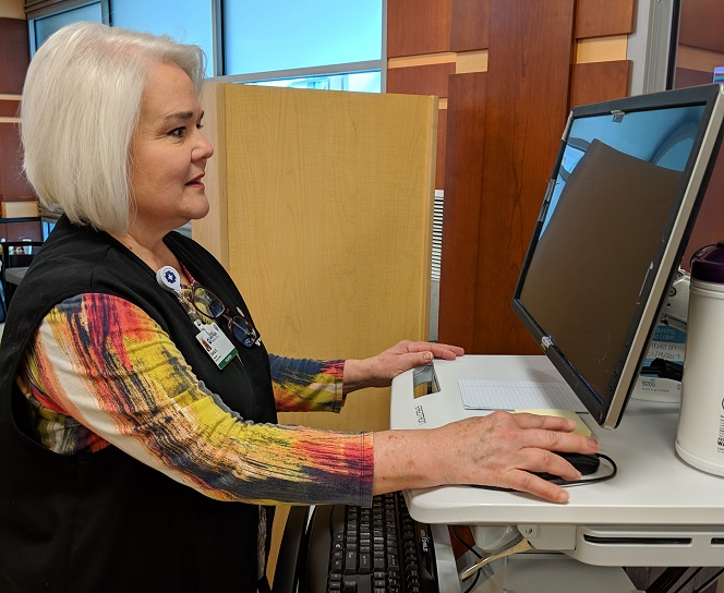 A volunteer uses a computer workstation in the Emergency Department waiting area.